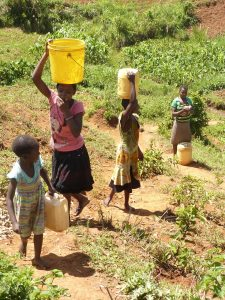kids coming uphill carrying water